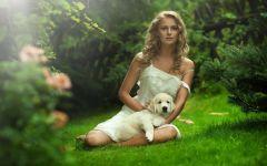 Девушка на лужайке со щенком золотистого ретривера